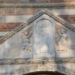Pavia, Basilica di San Pietro Cielo d'Oro - above the front entry door - Saint Michael the Archangel and two saints