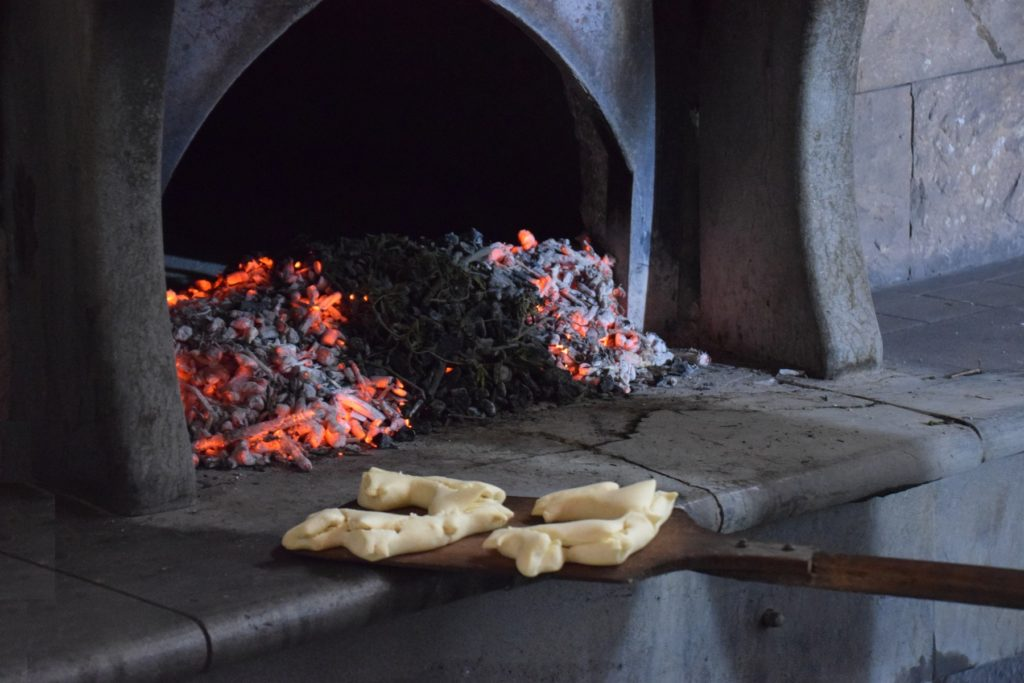 Samugheo - Pane Nostu - Antonello prepares to slide the risen loaves into the hearth. The bread is placed on the clean hearthstone behind the coals - deep inside