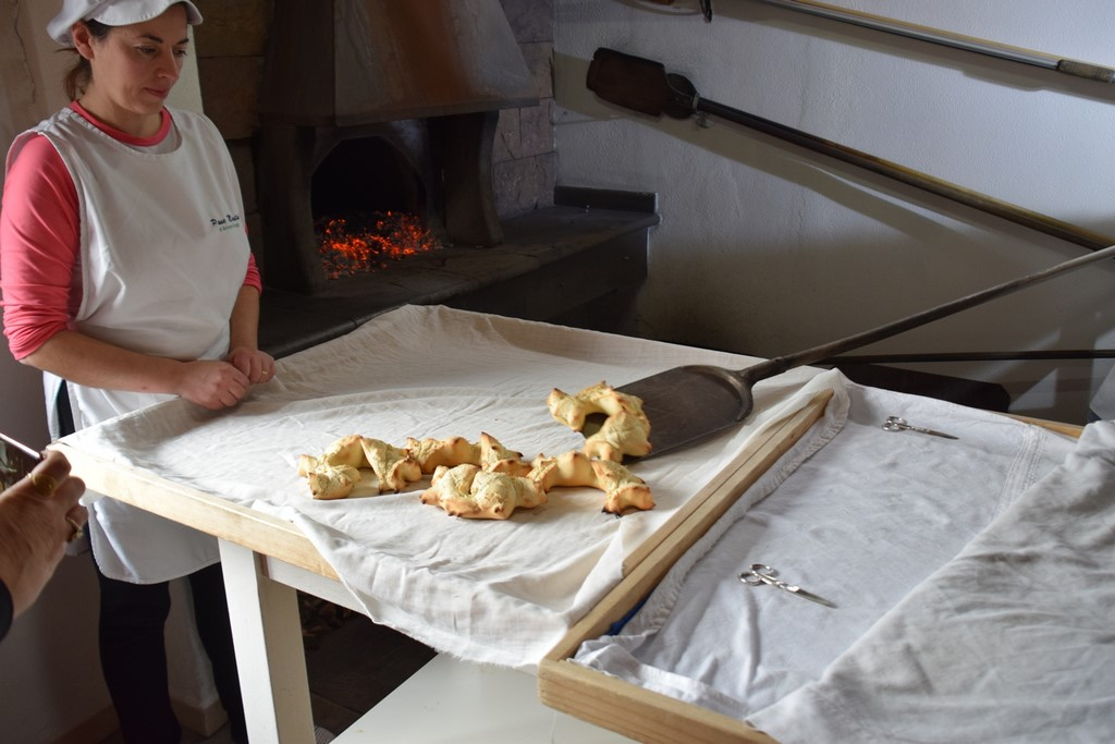 Samugheo - Pane Nostu - Antonello removes the hot bread from inside the oven while Giovanna watches